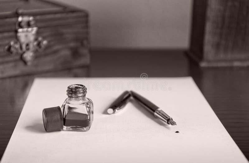 Pena de fonte de Borgonha, tinta azul e tinteiro na folha do Livro Branco fotografia de stock