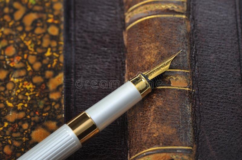 Pena de fonte com uma pena do ouro que encontra-se no livro velho fotografia de stock royalty free