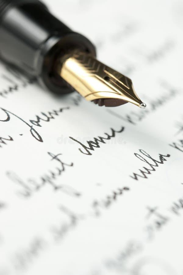 Pena de fonte do ouro na letra escrita mão fotografia de stock royalty free