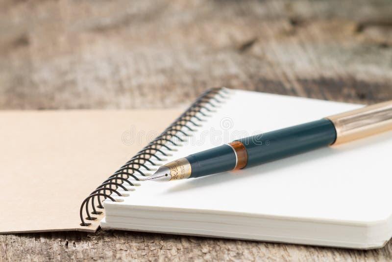 Pena de fonte dourada velha no caderno imagens de stock royalty free