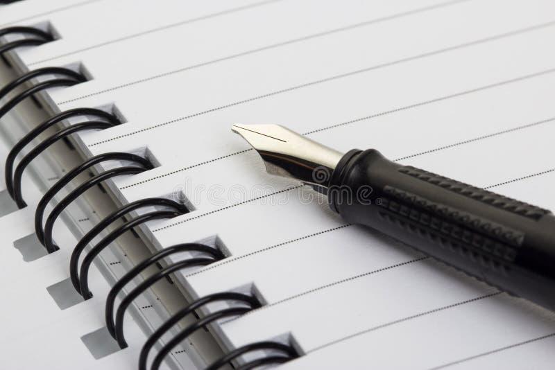 Pena de fonte e espiral em branco - bloco de notas encadernado imagens de stock