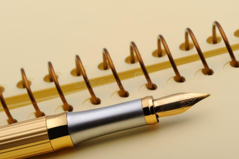 Pena de fonte em um caderno amarelo fotografia de stock royalty free