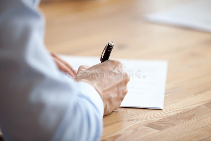 Pena de terra arrendada da mão do homem, escrevendo notas em encontrar o fim acima imagem de stock