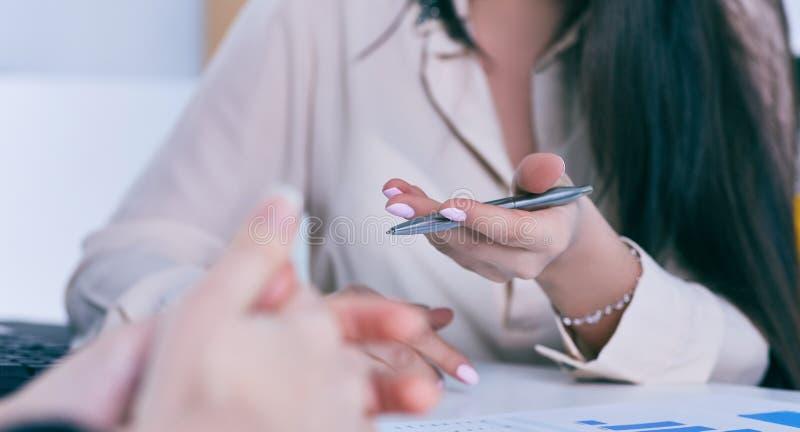 Pena de terra arrendada da mão da mulher de negócio e apontar no diagrama financeiro, gráfico durante a conferência que senta-se  fotos de stock royalty free
