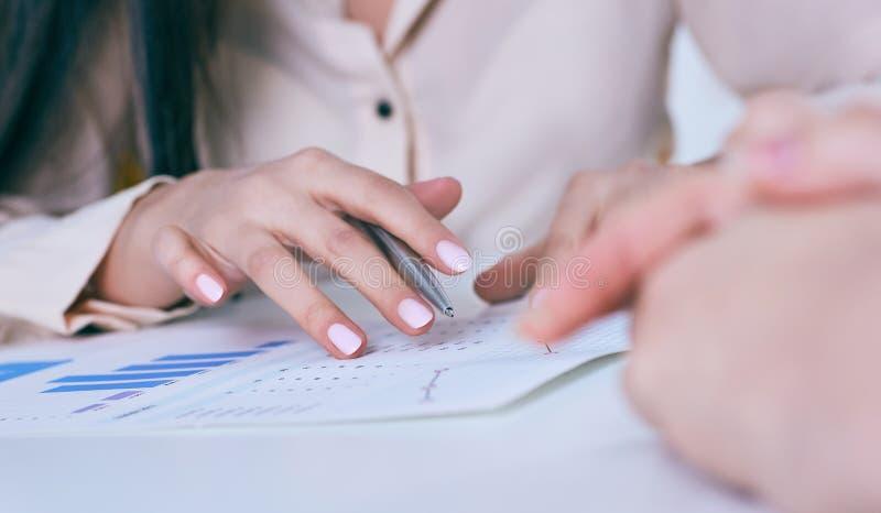Pena de terra arrendada da mão da mulher de negócio e apontar no diagrama financeiro, gráfico durante a conferência que senta-se  imagem de stock