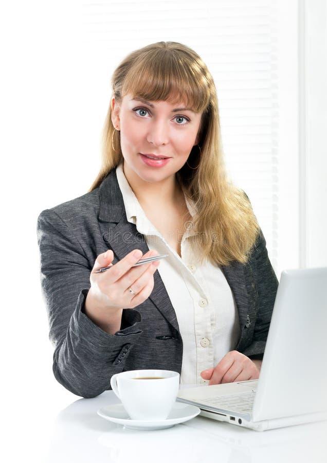 Pena de terra arrendada da mulher de negócios que senta-se na mesa fotografia de stock