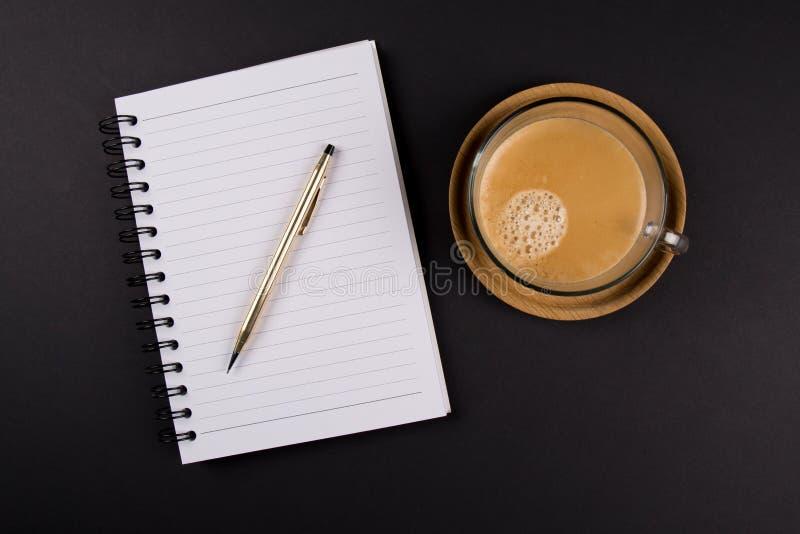 A pena do ouro, caderno, xícara de café em uma bandeja de madeira, na tabela preta, disparou de cima de imagens de stock royalty free