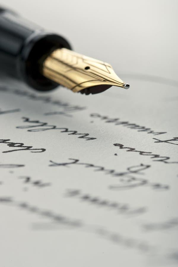 Pena do ouro na letra escrita mão fotos de stock