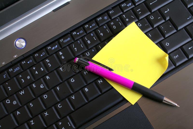Pena e bloco de notas no teclado foto de stock