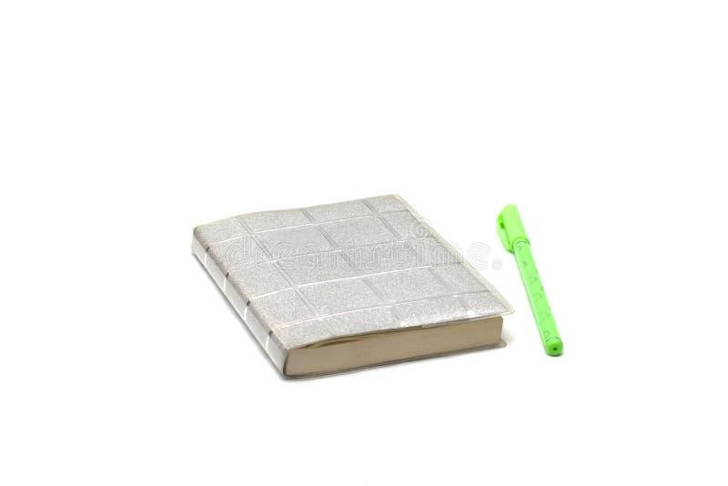 Pena e caderno verdes em um fundo branco fotos de stock royalty free