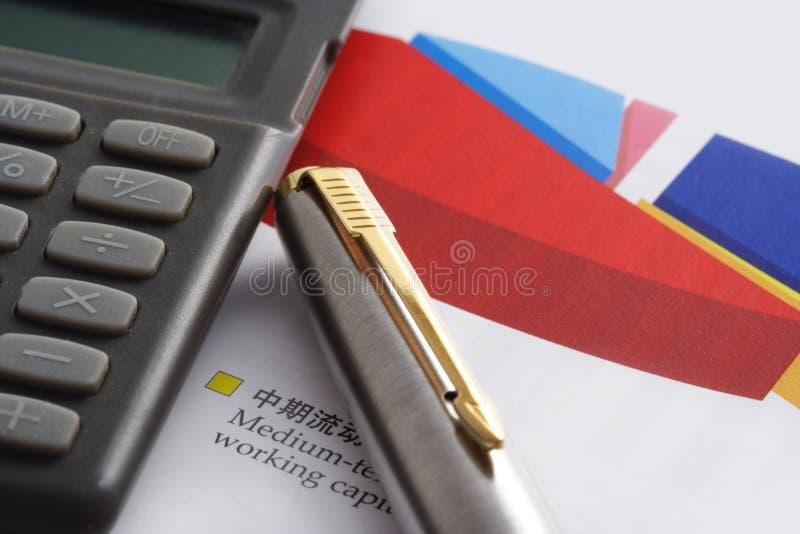 Pena e calculadora no gráfico da torta fotografia de stock royalty free