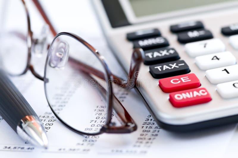 Pena e vidros da calculadora do imposto foto de stock