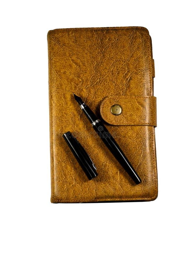 Pena fechado do caderno e de fonte isolada no branco imagens de stock royalty free