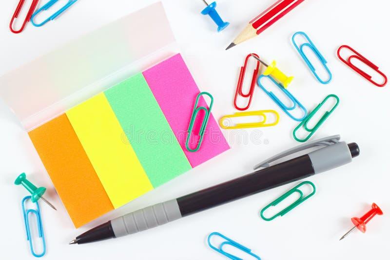 Pena, lápis, clipes, percevejos e etiquetas coloridos no desktop branco imagens de stock