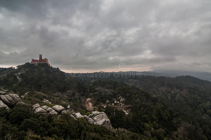 Pena National Palace in the municipality of Sintra. Dark, cloudy sky over the hilltop with romanticist Pena National Palace (Palácio Nacional da Pena) in the stock photography