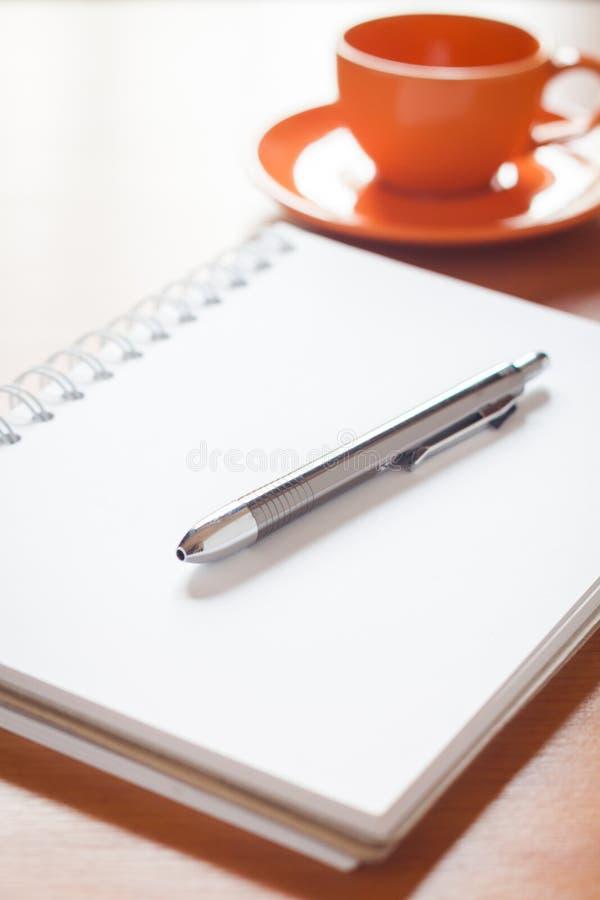 Pena no caderno branco vazio aberto com o copo de café na mesa foto de stock royalty free