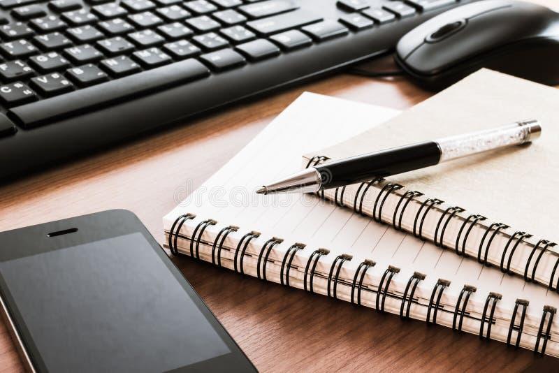 Pena no caderno com teclado, rato e telefone celular de computador fotografia de stock royalty free