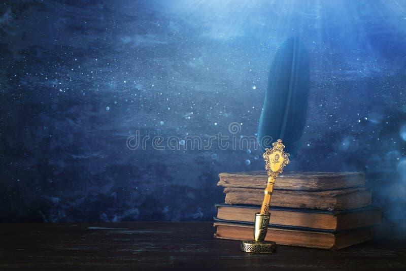 Pena velha da tinta da pena da pena com tinteiro e os livros velhos sobre a mesa de madeira na frente do fundo preto da parede Es ilustração royalty free