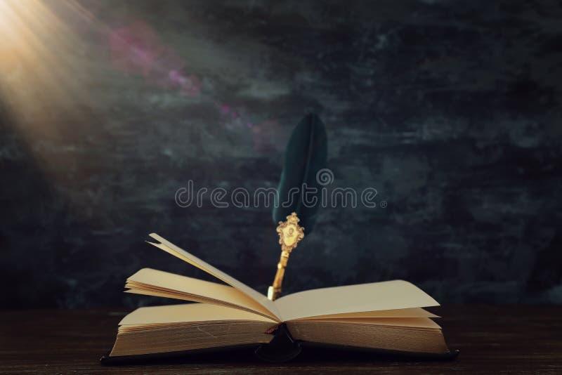 Pena velha da tinta da pena da pena com tinteiro e os livros velhos sobre a mesa de madeira na frente do fundo preto da parede Fo fotografia de stock
