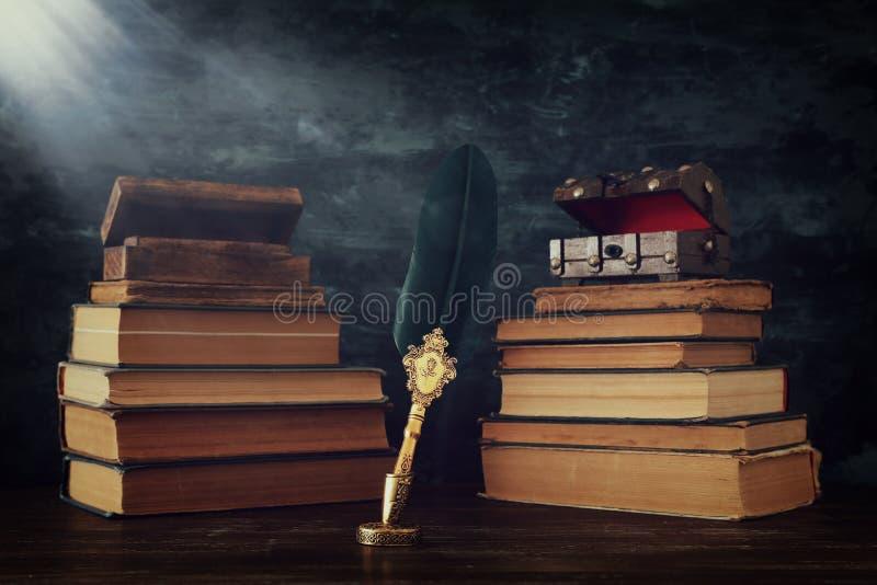 Pena velha da tinta da pena da pena com tinteiro e os livros velhos sobre a mesa de madeira na frente do fundo preto da parede Fo ilustração do vetor