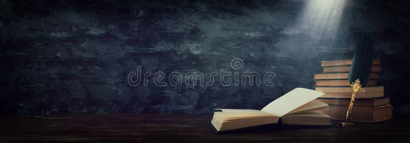 Pena velha da tinta da pena da pena com tinteiro e os livros velhos sobre a mesa de madeira na frente do fundo preto da parede Fo ilustração royalty free