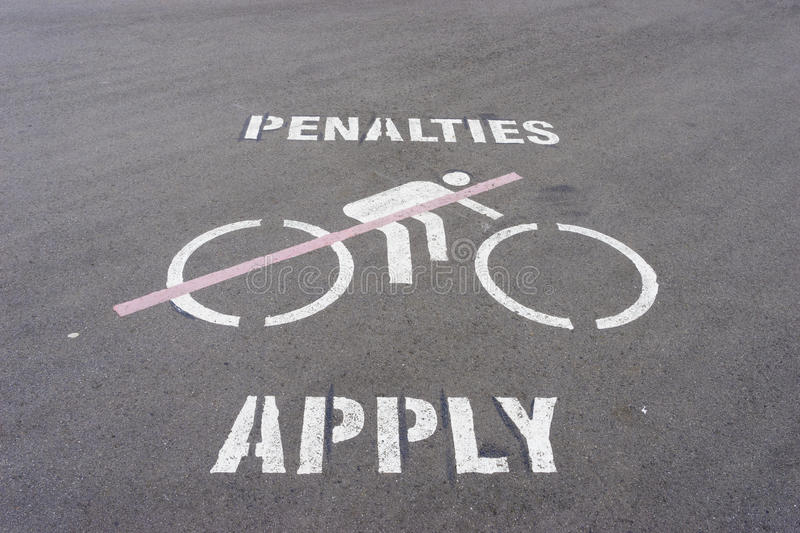 Penalties apply and no cycling sign on the road. Penalties apply and no cycling wordings and graphics on the road stock images