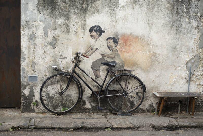 PENANG, MALAYSIA - JULY 2018: famous 3d streetart of a bicycle a. Georgetown, PENANG, MALAYSIA - JULY 31 2018: famous 3d streetart of a bicycle an two kids in royalty free stock image