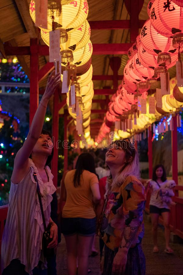 Penang, Malaysia - March 1, 2019: Sin Hui shows Stacie Yokiel the significance of the Chinese New Year lanterns at the Kek Lok Si royalty free stock photos