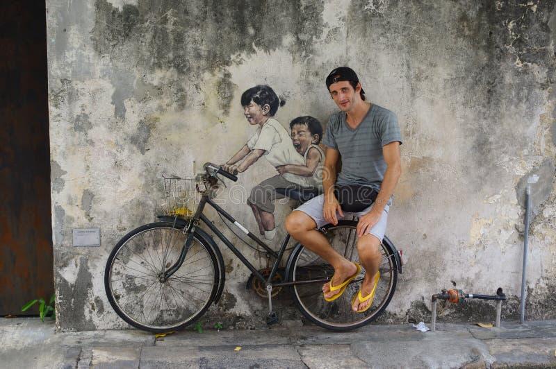 PENANG, MALEISIË - APRIL 18, 2016: De lokale toerist stelt voor Straat Muurschildering tittle ` Kleine Kinderen op een Fiets stock afbeeldingen