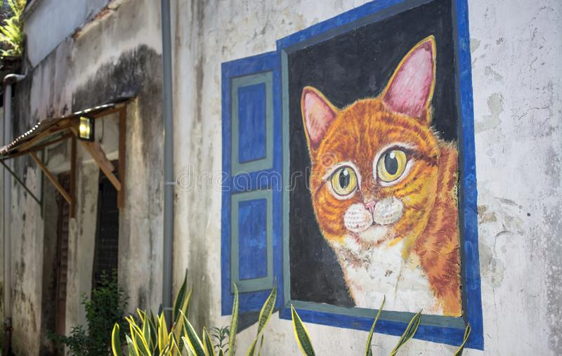 Penang Street Art, Georgetown, Penang, Malaysia. October 2016: World famous street art with big cat inside open window wall stock images
