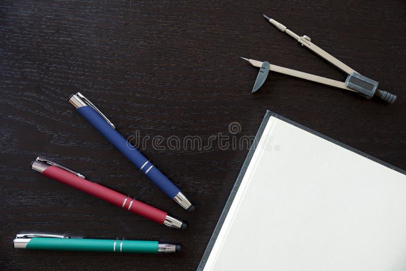 Penas, caderno e compasso de desenho a personalizar imagem de stock