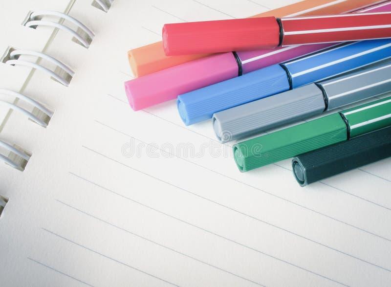 Penas coloridas no caderno imagem de stock