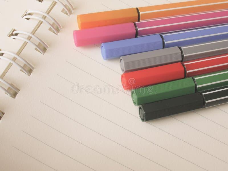 Penas coloridas no caderno foto de stock