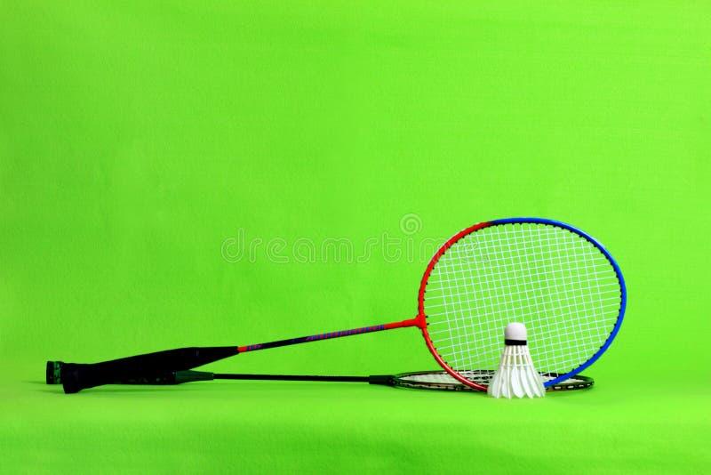 Penas da raquete e da peteca de badminton na luz - fundo verde com espaço do texto foto de stock royalty free