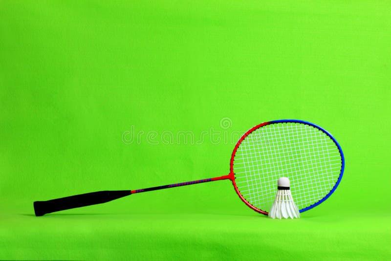 Penas da raquete e da peteca de badminton na luz - fundo verde com espaço do texto imagens de stock