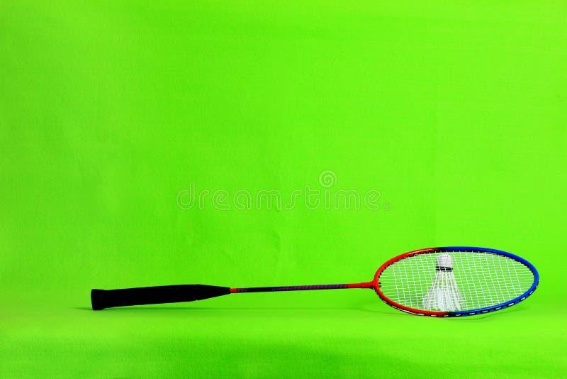 Penas da raquete e da peteca de badminton na luz - fundo verde com espaço do texto fotografia de stock royalty free