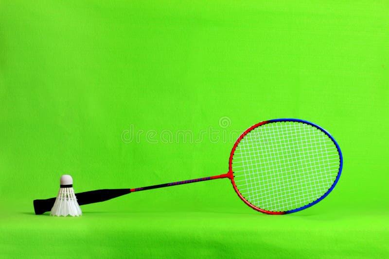 Penas da raquete e da peteca de badminton na luz - fundo verde com espaço do texto foto de stock