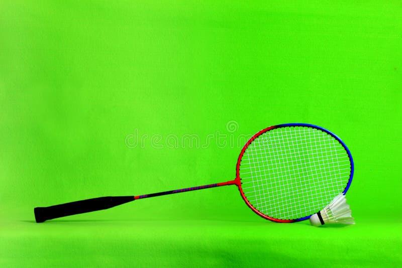 Penas da raquete e da peteca de badminton na luz - fundo verde com espaço do texto imagem de stock