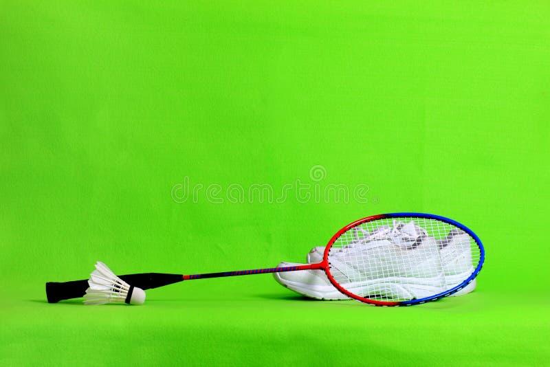 Penas da raquete e da peteca de badminton na luz - fundo verde com espaço do texto fotos de stock royalty free