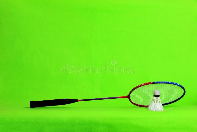 Penas da raquete e da peteca de badminton na luz - fundo verde com espaço do texto imagens de stock royalty free