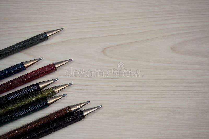 Penas de esferográfica do brilho na tabela de madeira imagem de stock