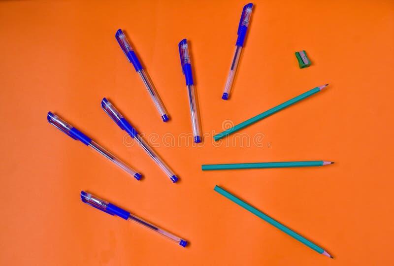 Penas e lápis brilhantes no fundo alaranjado fotografia de stock royalty free