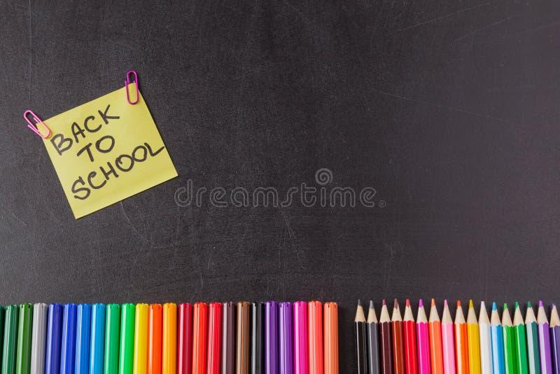 Penas, lápis e título coloridos de volta à escola escrita no pedaço de papel no quadro preto imagens de stock
