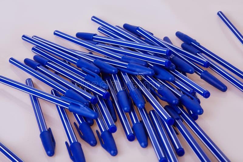Penas plásticas azuis isoladas no branco imagem de stock