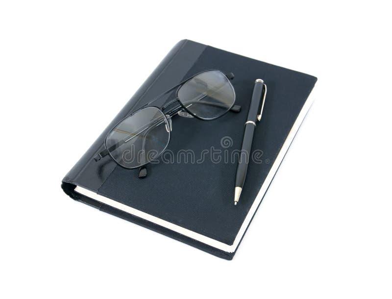 Penboek en glazen op witte achtergrond wordt geïsoleerd die royalty-vrije stock foto