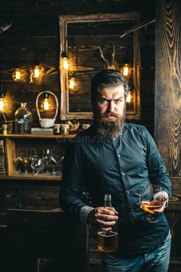 penchant d'alcool Alcoolique avec la bouteille et le whiskey potable en verre la nuit photo stock