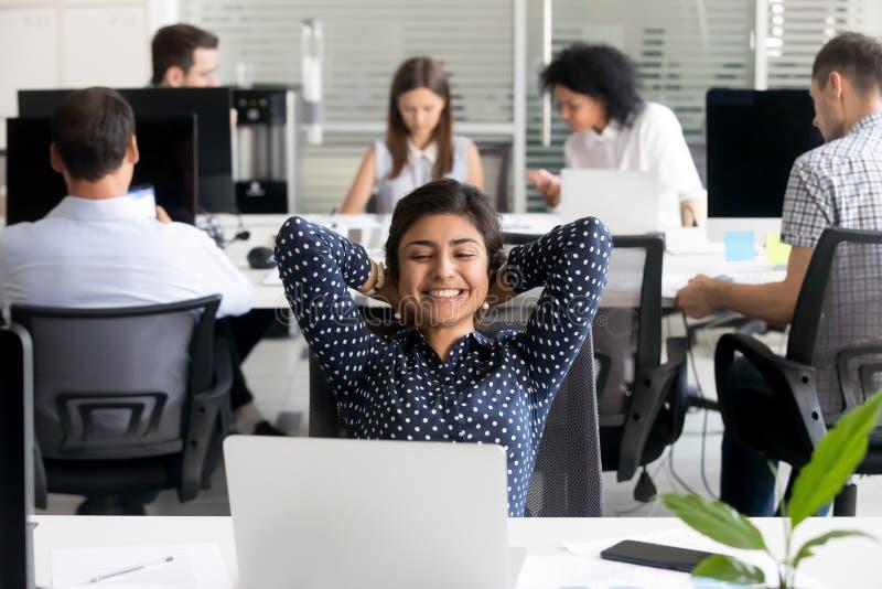 Penchement de détente de sourire des employés féminins indiens de retour sur le lieu de travail photos libres de droits
