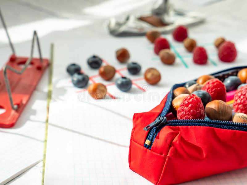 Pencil case and tic-tac-toe wtih berries, nuts and chocolate on a lunch break. Learn and plya. Back to school concept. Pencil case packed with berries, nuts stock photography