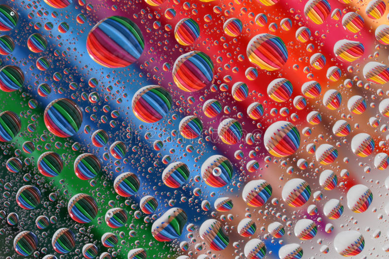 Pencil Crayons through Water Droplets (2). Colourful, aligned pencil crayons, reflected through random water droplets. This image could provide a fun and unique stock photos