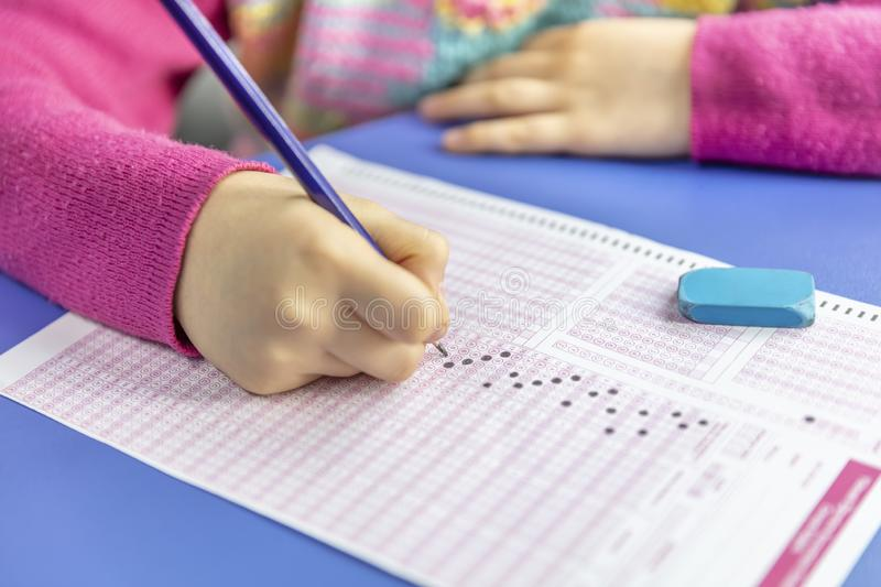 Hand student testing in exercise and taking fill in exam carbon paper computer sheet with pencil at school test room, education. Pencil drawing selected choice royalty free stock photo
